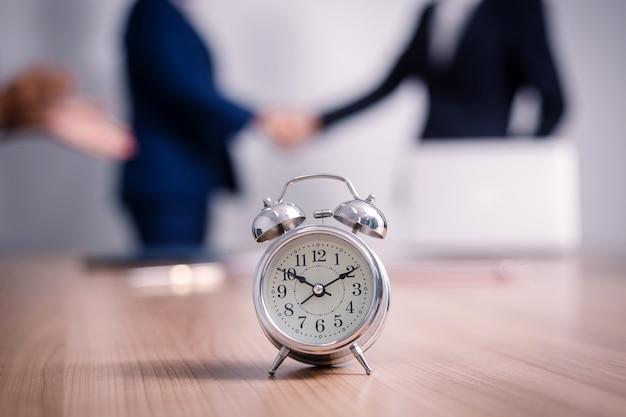 セミナー室のビジネス人々とテーブルの上の目覚まし時計。企業の成功ブレインストーミングチームワークを満たす Premium写真