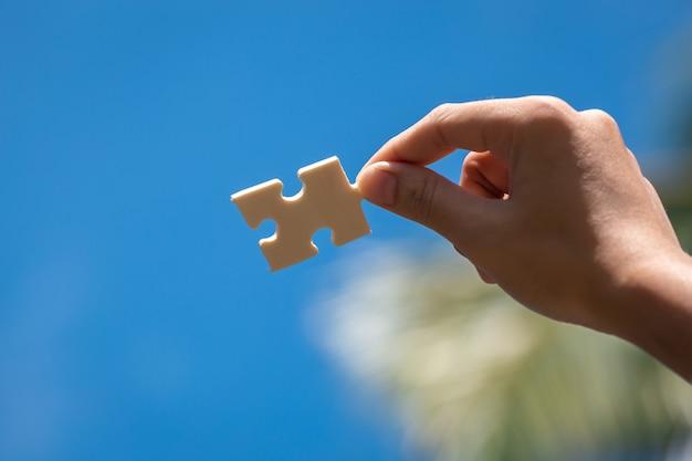 青い空を背景に女性の手でジグソーパズルのピース Premium写真