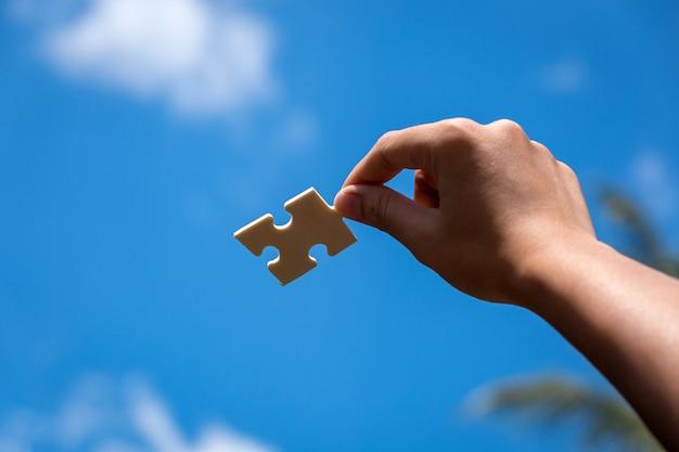 青い空と女性の手でジグソーパズルのピース Premium写真