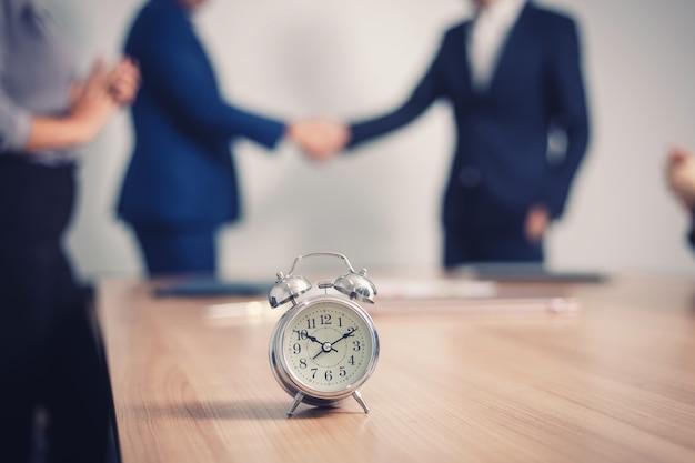 セミナー室のビジネス人々とテーブルの上の目覚まし時計。 Premium写真