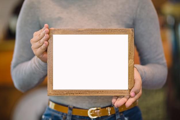コーヒーショップで空白の木製フレームを保持している女性 Premium写真