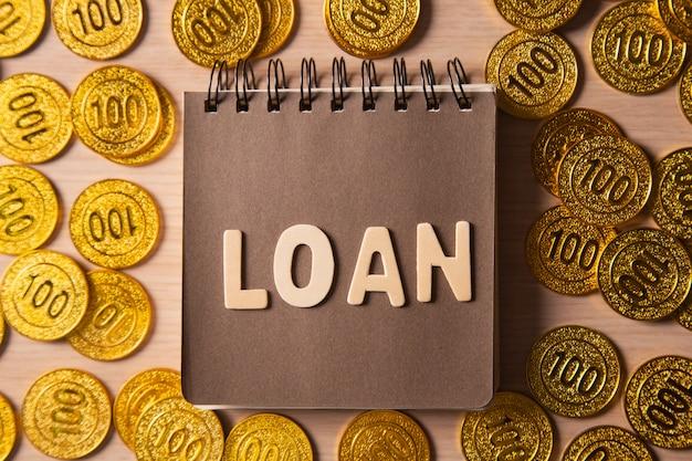 黄金のコインは、ローンをレタリングと背景をスタックします。 Premium写真