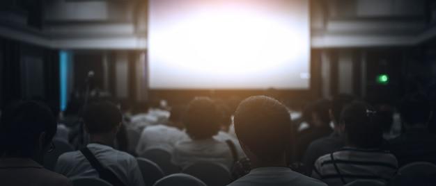 クラウンは、ビジネス会議で講演するスピーカーを聞いています。 Premium写真