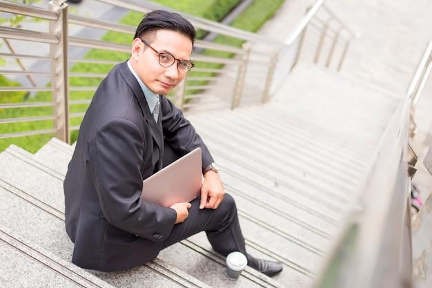 ビジネスの男性は、近代的な都市で彼のラップトップ屋外で働いています。 Premium写真