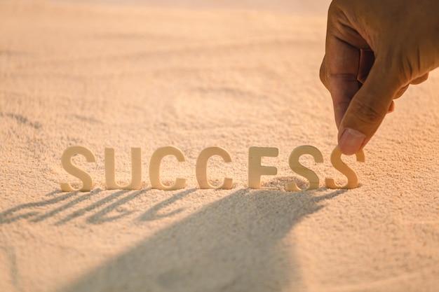 Успех - концепция бизнес-мотивации с деревянным алфавитом на песчаном пляже. вдохновляющие цитаты. мотивационные слова Premium Фотографии