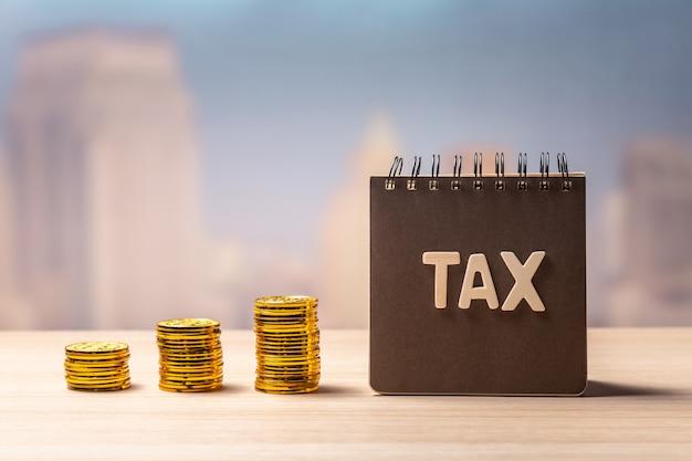 Налоговая надпись на блокноте и стопки монет Premium Фотографии