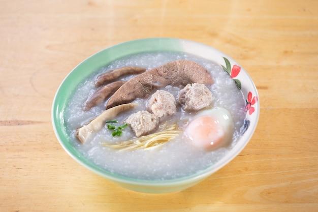 Рисовый отвар со свининой на деревянном столе Premium Фотографии