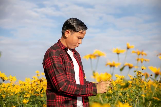 Колхозники осматривают солнечные летние цветы колхоза. Premium Фотографии