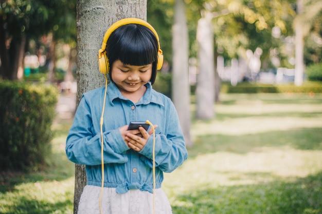 Дети концепции и технологии - улыбающаяся девушка в наушниках слушает музыку Premium Фотографии