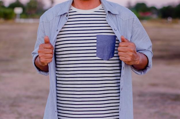 ビジネスマンは、白黒の縞模様のシャツを飾るためにシャツを開けています。 Premium写真