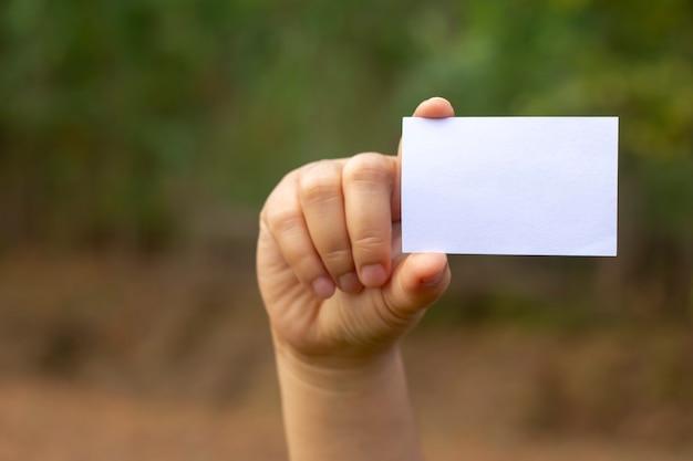 自然の背景に手に空白の名刺。モックアップ Premium写真