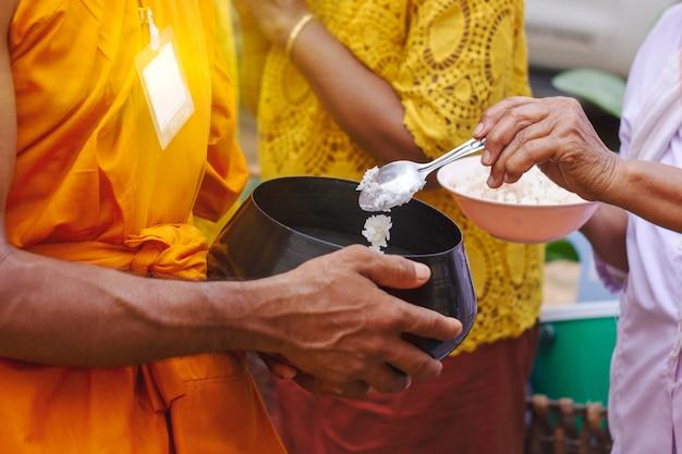 Тайцы кладут еду в чашу для подаяний монаха в конце буддийского великого поста Premium Фотографии