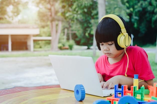 ノートパソコンとヘッドフォンを使用してアジアの女の子 Premium写真