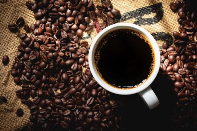 焙煎コーヒーと白いセラミックコーヒーカップでトップビューブラックコーヒー Premium写真