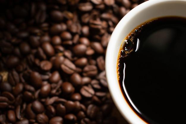 ぼやけローストコーヒー豆と白いセラミックコーヒーカップのブラックコーヒー Premium写真