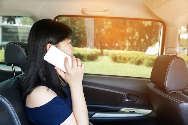 車で携帯電話を持つ美しい女性 Premium写真