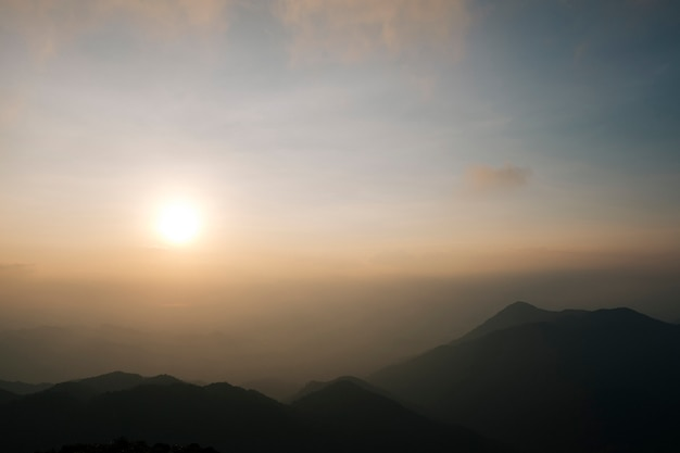 軽い朝の霧、日の出、そして壮観な山脈が交互に並んでいます。 Premium写真