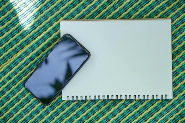 電話とスマートフォン市松模様のマットの上に置かれたメモ帳 Premium写真