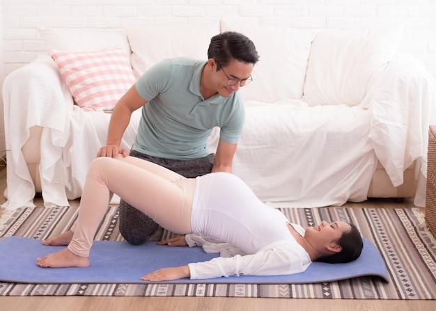 Муж помогает своей беременной жене делать упражнения. Premium Фотографии