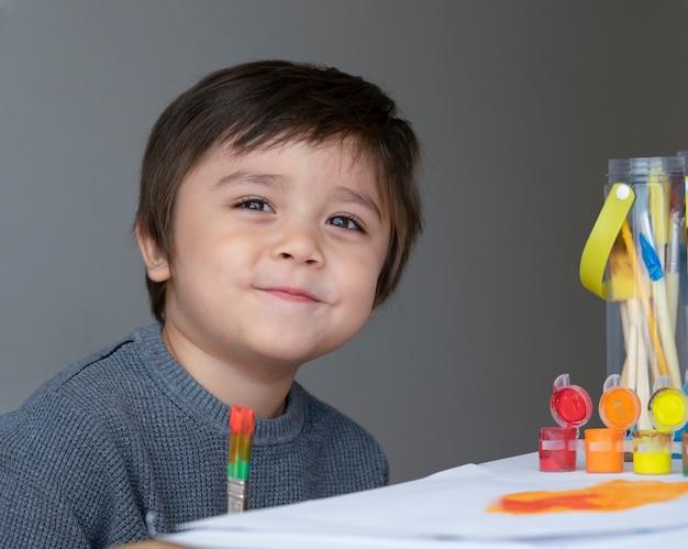 楽しんで子供男の子の肖像画紙の上の水の色を塗る Premium写真