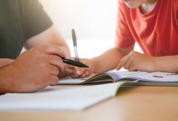 Папа и сын вместе делают домашнее задание, учитель учит маленького мальчика, как писать. Premium Фотографии