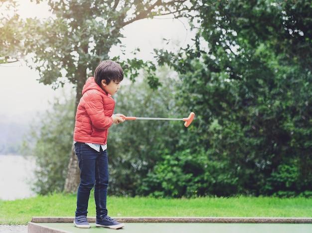 公園、休日にゴルフをしているアクティブな子供男の子、彼の休暇の屋外活動を楽しんでいる子供たちでミニゴルフをして幸せな子供の肖像画 Premium写真