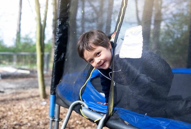 Счастливый школьный ребенок, поднимающийся в сторону батута Premium Фотографии