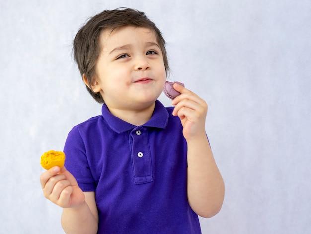 マカロンを食べて喜んでいる子供の肖像画 Premium写真