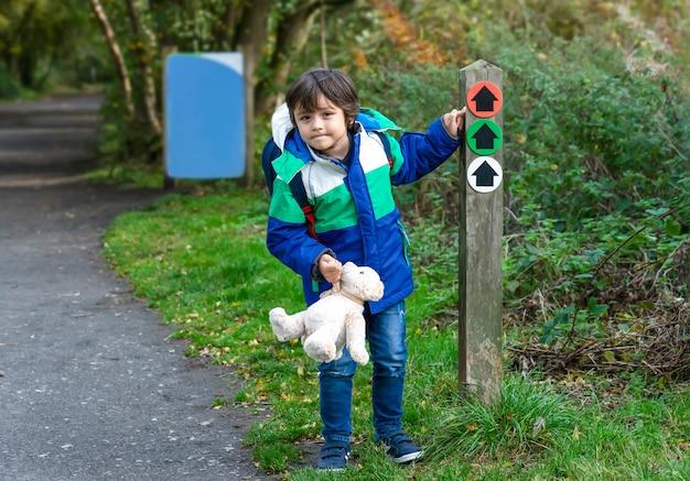 方向矢印記号に人差し指を探しているテディベアを保持している屋外のポートレートの子供 Premium写真