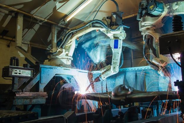 Командное робототехническое сварочное производство промышленная автомобильная часть на заводе Premium Фотографии