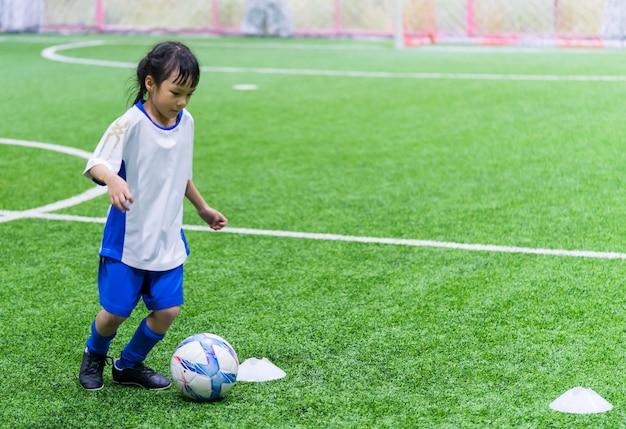 Маленькая азиатская девушка тренируется в помещении футбольного поля Premium Фотографии