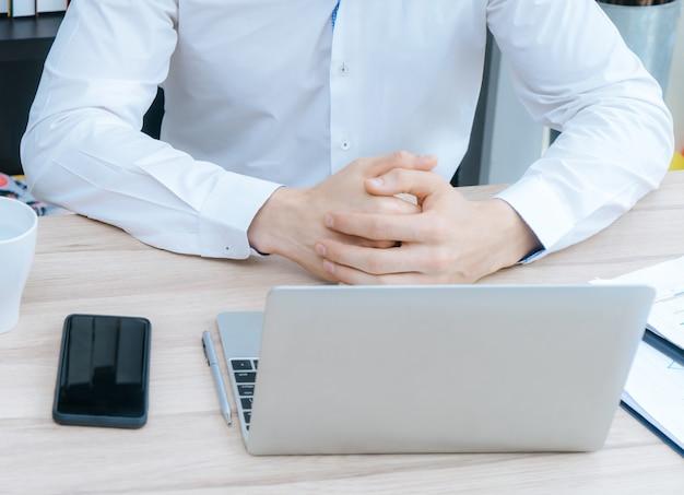 ビジネスマンは、窓の上の机の上でコンピュータ上で作業しています Premium写真