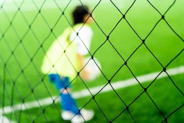 Маленькая азиатская девушка тренируется в закрытом футбольном поле размытые Premium Фотографии