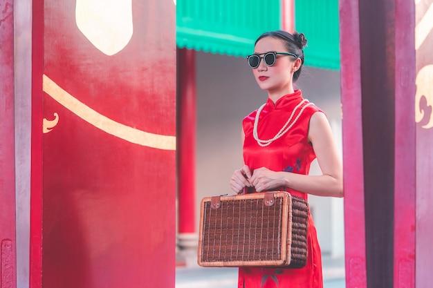 木製の荷物を持つアジアの中国の女の子ビンテージアジア旅行の概念 Premium写真