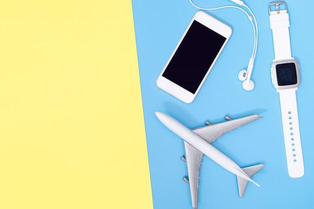 Туристические аксессуары предметы и гаджеты вид сверху плоские на синем желтом Premium Фотографии