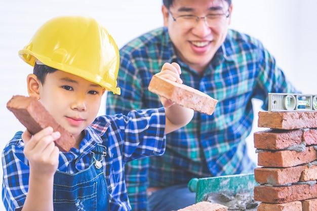 Азиатский мальчик учит, как построить кирпичную стену от своего отца строителя, отец инженера учит своего сына в ремонте дома для концепции образа жизни семьи. Premium Фотографии