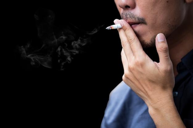 Взгляд со стороны сигареты молодого бородатого человека куря на черной предпосылке. Premium Фотографии
