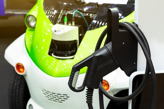 都市の通りに駅を充電する電気自動車で駐車場に充電している電気自動車。 Premium写真