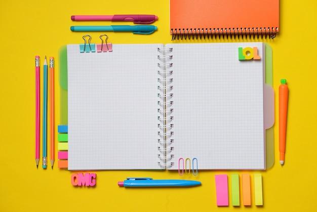 黄色のチョークでオフィスと学生用品とカラフルなオープンコピー本。 Premium写真