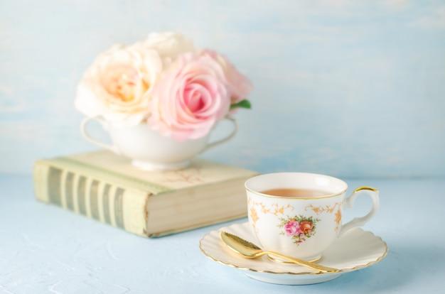Крупным планом чашку чая с цветами и книги на синем Premium Фотографии