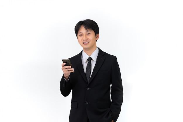 Красивый азиатский бизнесмен используя мобильный телефон на белой предпосылке Premium Фотографии