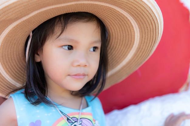 大きな帽子をかぶってかわいい女の子を閉じる Premium写真