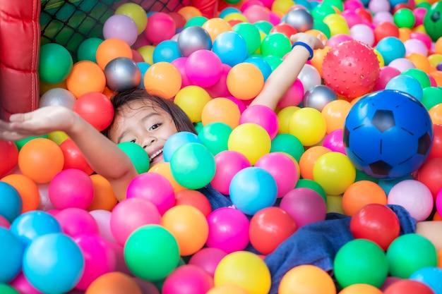 色のプラスチックボールを持つ少女。面白い子が室内で楽しんでいます。 Premium写真
