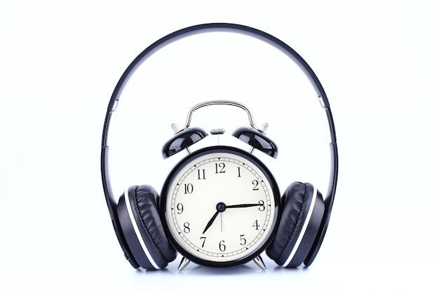 白い背景で隔離のヘッドフォンとレトロな黒い目覚まし時計。 Premium写真