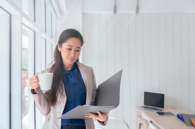 ビジネスの女性一杯のコーヒーを飲むとオフィスの窓に立っています。 Premium写真