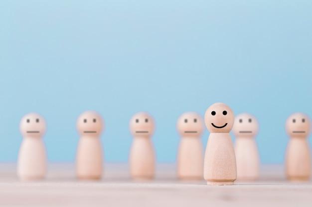 笑顔の絵文字アイコンに直面する木製人間の幸せのシンボル Premium写真