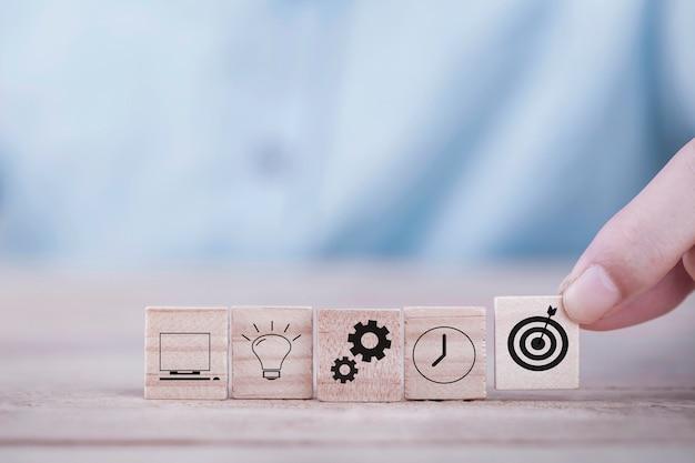 Бизнесмен выбирает цель иконы смайлик с символом стрелки на деревянный блок Premium Фотографии
