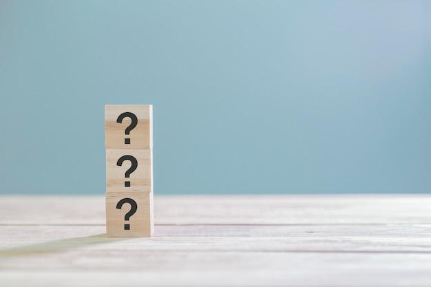 Деревянный куб с знаком знак вопроса на деревянный стол с копией пространства Premium Фотографии