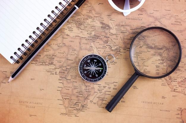 Компас на старинные карты с увеличительным стеклом и книги. план путешествий и приключений концепция. Premium Фотографии