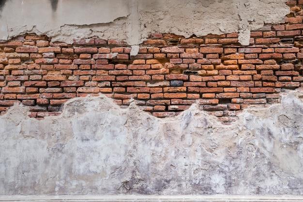 Пустая старая текстура кирпичной стены. стены распадаются из красного кирпича. фасад здания с поврежденной штукатуркой. Premium Фотографии